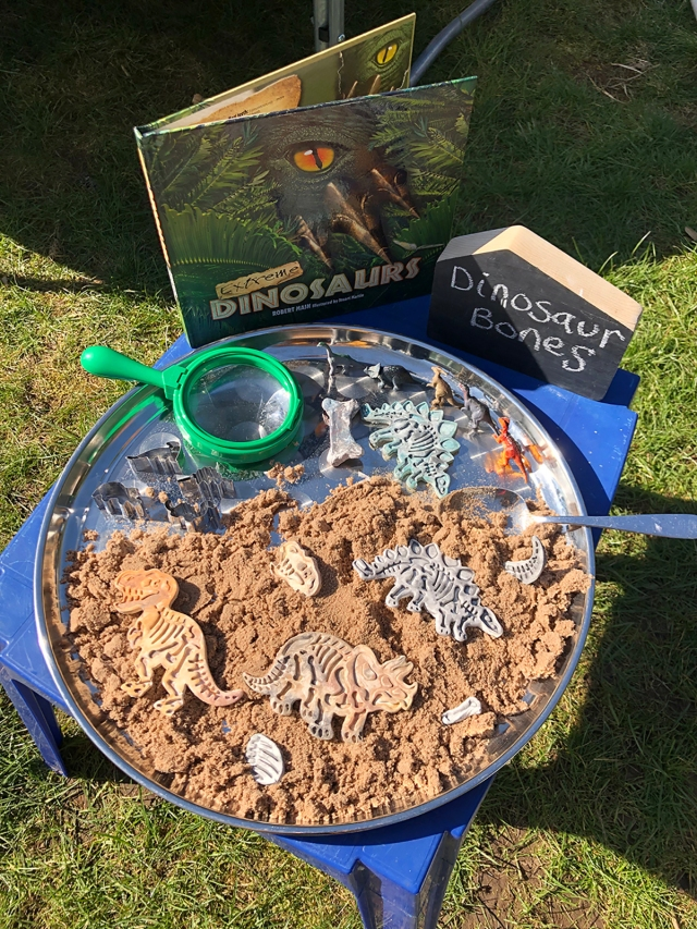Air dry clay dinosaur bones in a small world discovery tray
