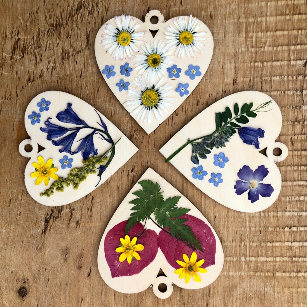 nature collecting and treasures, pressed flowers displayed on wooden shapes for hanging - pressed flower craft.